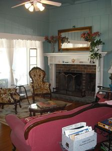 Living room for 6 people to visit with a fireplace & a large picture window.