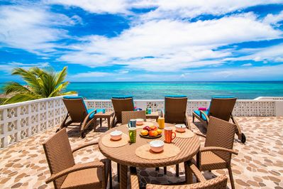 Oceanfront patio with chaise lounges and alfresco dining area