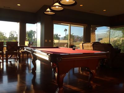 Inside the house looking out all glass windows to see the golf course play pool