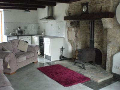 The open-plan ground floor with antique wood-burner and Charantais fireplace.