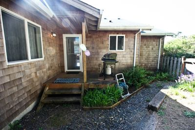 Fenced backyard with deck, gas BBQ and gravel pathway around the house
