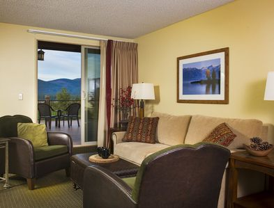 A well furnished living room with a balcony and mountain view.