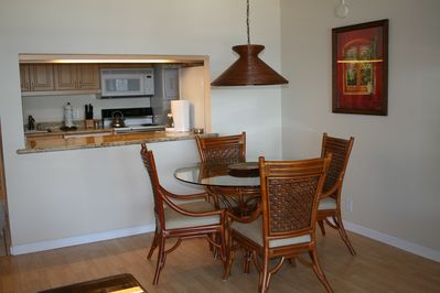 A view of the dining area featuring seating for 4 and a peek into the kitchen.