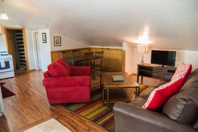 Living and dining areas with comfortable sofa chair, leather sleeper sofa and TV