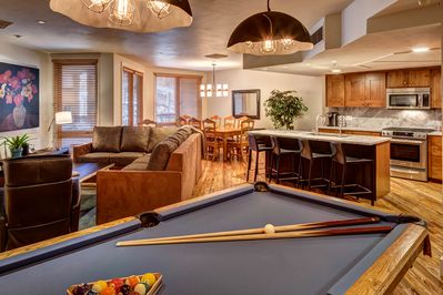Pool table with view of kitchen, living room, and private balcony.