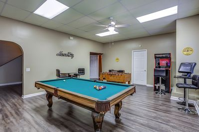 Game room with pool table, foosball, arcade games and record player stereo.