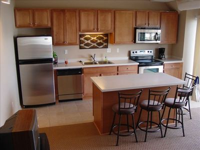 Upgraded Kitchen with Stainless Steel, Ceramic Tile and Island with Stools