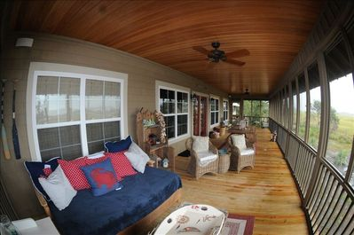The large screened porch has an elegant bed and large table to enjoy the view