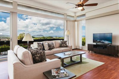 Two white couches placed in front of a small flat screen TV in the living room with large windows facing Diamond Head