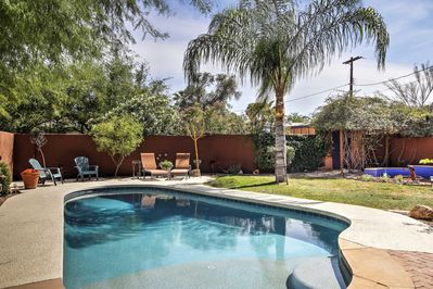 The home's quarter-acre lot features a swimming pool, hot tub & outdoor kitchen.