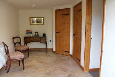 A spacious entrance hall with downstairs cloakroom opening off it.