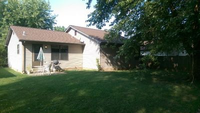 Large shaded back yard with patio set and shed