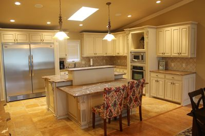 Kitchen with large island.  Double refrigerator.