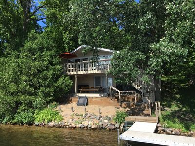 The cabin is right on the water and is surrounded by oak trees.