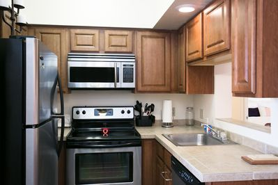Kitchen nook, showing stainless steel appliances and pass through on right to breakfast bar