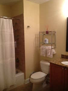 Hall bath with tub/shower enclosure.  Tile & granite