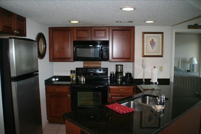 Well stocked kitchen with granite countertops