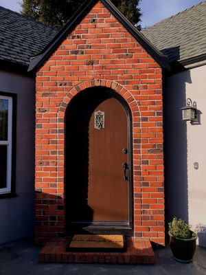 Our front door with handsome brickwork and a vintage peephole!