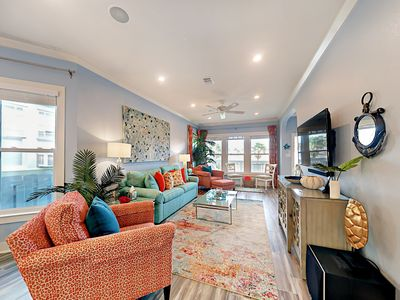 """Living Area - Enjoy your favorite shows on the 55"""" wall-mounted TV. Complimentary Wi-Fi is provided."""