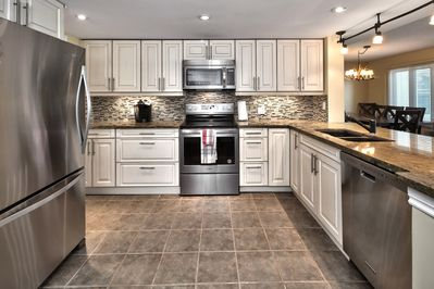 Renovated kitchen has upgraded cabinetry, stainless steel appliances and granite