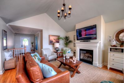 Main level living room with a gas fireplace and 60 inch television