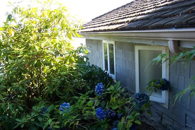 The outside of the cottage is surrounded by a lovely garden of flowers.