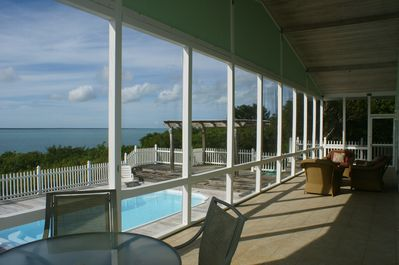 Screened in porch overlooking the pool deck and Sea of Abaco.