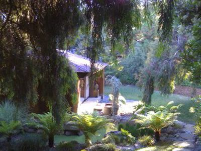 The lush landscaping surrounding the cottage includes a trickling stream.