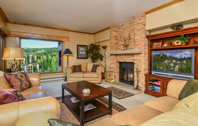 Beautifully appointed living room with wood burning fireplace and mountain views