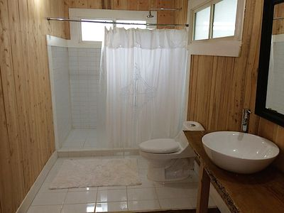 Spacious bathroom with hot water shower.