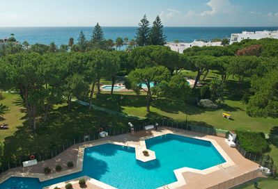 Partial aerial view of beach-front Club Playas del Duque gardens. We own 5 apt's