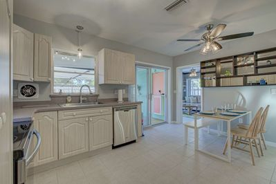 Large kitchen with stainless appliances and solid natural stone counters.