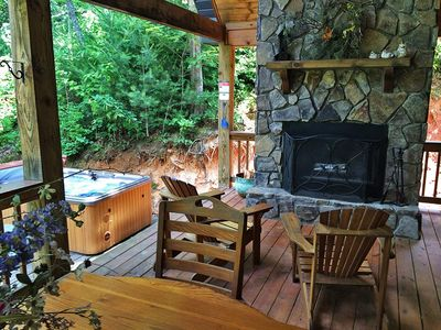 Outside fireplace (firewood provided), dining table, and hot tub.