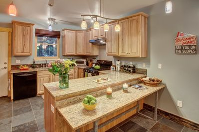 Kitchen - granite counter tops, a gas stove, modern appliances, and bar seating