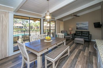 Dining Area/Living Room - This condo is a totally new unit, completely renovated in 2018.  The dining area and living room have wood grain tile flooring.  You enjoy a view of the courtyard and pool through the sliding doors to the balcony.