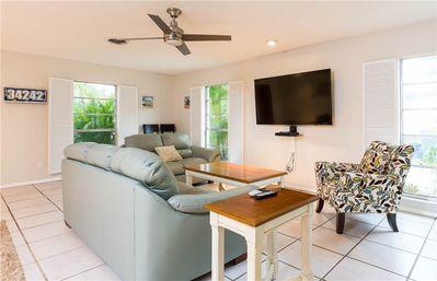 """Take it easy - Window shutters to let the fresh air and sunshine in. Tiled floors that feel blissfully cool underfoot. Plush seating for sprawling out on as you watch a movie on the 60"""" HDTV. The living room has everything you need to relax in style."""