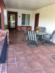 Fenced in covered front courtyard with patio table and 4 chairs.