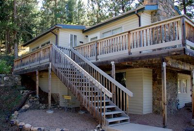 The Fir House – Exterior view of deck and stairs. Forested mountain backdrop.