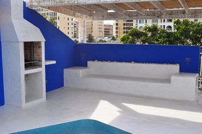 Swimming pool with BBQ and bench to sit and relax