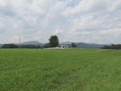 Hay field in front of Farm House. Mountains in background.