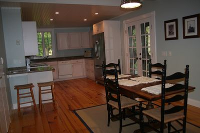 A cooks kitchen with French doors leading to the covered porch