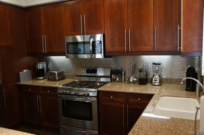 Granite countertops with stainless steel appliances and backsplash