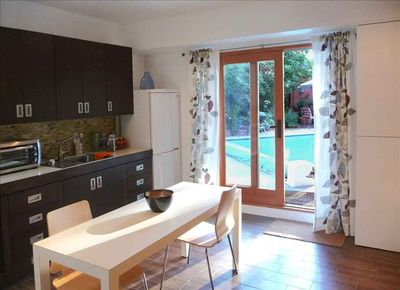 Fully equipped kitchen with French doors that open out to the pool and patio.