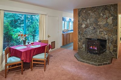 Nice dining area with views of the redwoods, cozy fireplace.