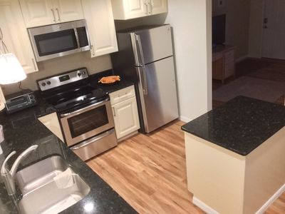 Fully stocked kitchen with dishwasher, disposal, microwave, and flat top range