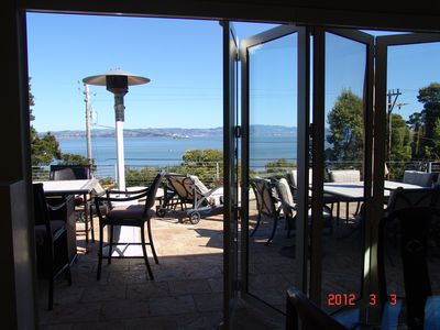 View from Living room with folding glass doors partly open and bay in background