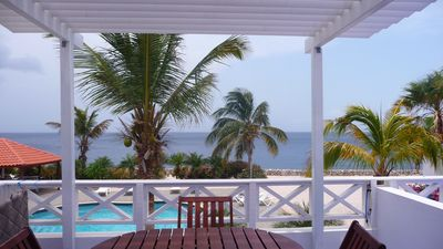 View of sea and pool from townhome. Notice shade pergola and wood furniture