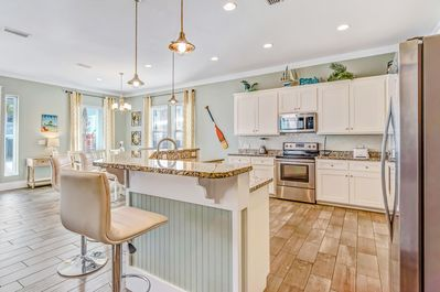 A fully stocked kitchen with stainless steel appliances.