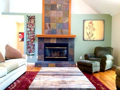 Cathedral ceilings in great room brings in light for the art and slate fireplace