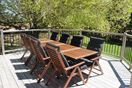Expansive outdoor teak patio set that can accommodate up to ten people.